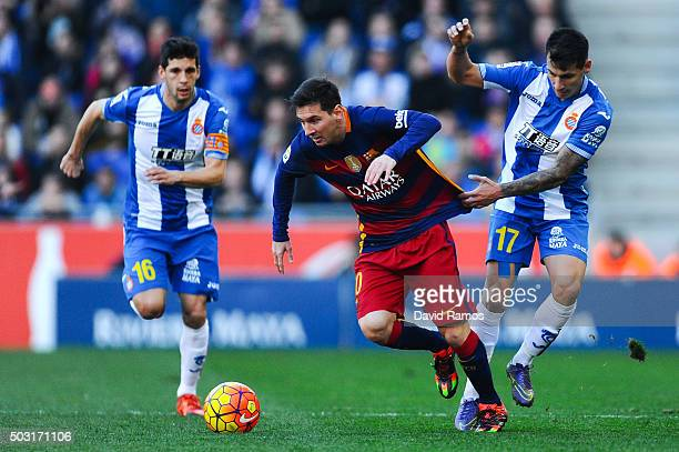 Lionel Messi of FC Barcelona competes for the ball with Hernan Perez and Javi Lopez of RCD Espanyol during the La Liga match between RCD Espanyol and...