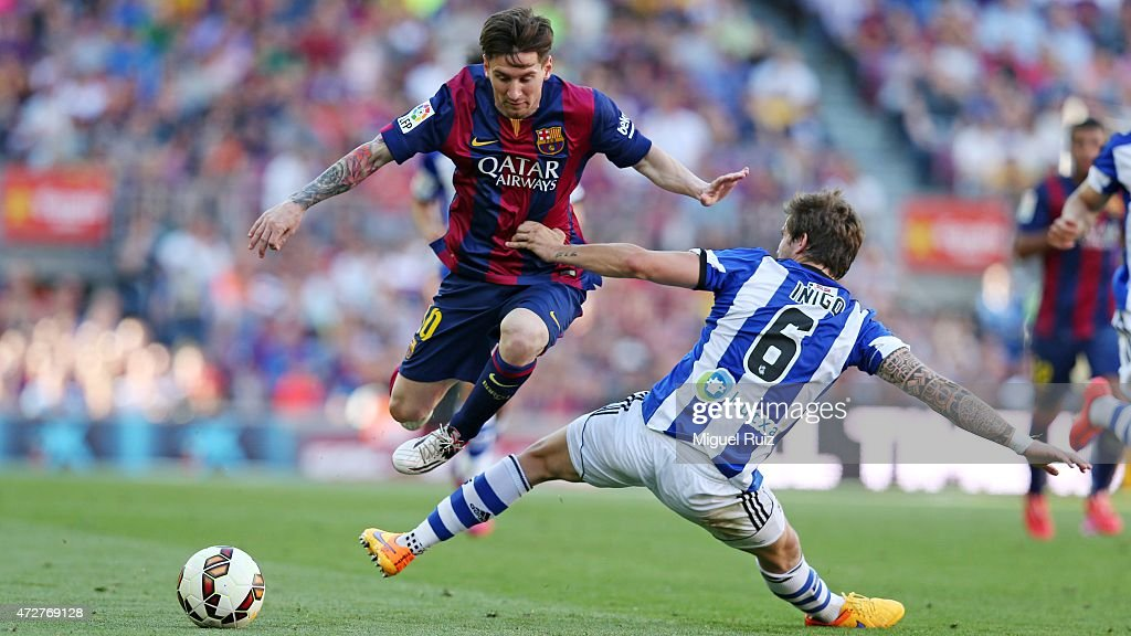 Lionel Messi of FC Barcelona competes for the ball with Iñigo Martinez of Real Sociedad de Futbol during the La Liga match between FC Barcelona and...