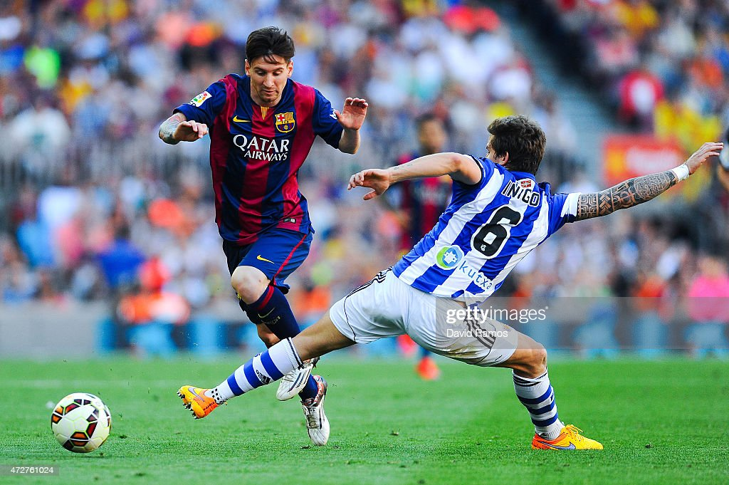 Lionel Messi of FC Barcelona competes for the ball with Inigo Martinez of Real Sociedad de Futbol during the La Liga match between FC Barcelona and...
