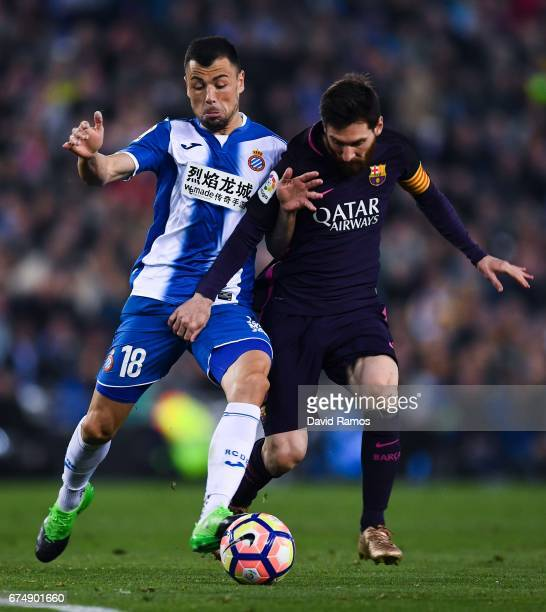 Lionel Messi of FC Barcelona competes for the ball with Javi Fuego of RCD Espanyol during the La Liga match between RCD Espanyol and FC Barcelona at...