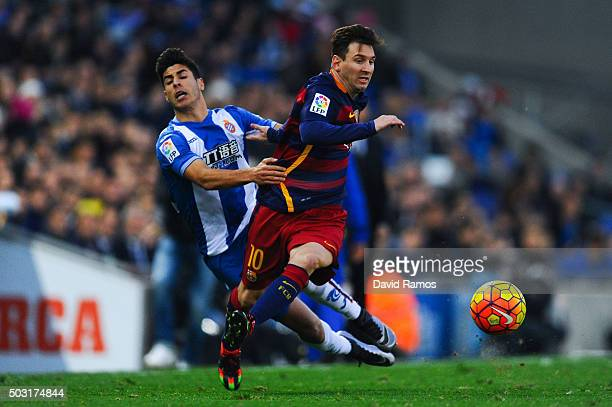 Lionel Messi of FC Barcelona competes for the ball with Marcos Asensio of RCD Espanyol during the La Liga match between RCD Espanyol and FC Barcelona...