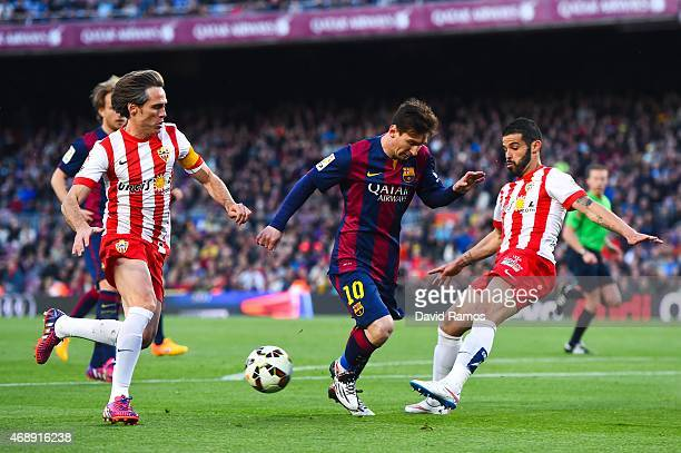 Lionel Messi of FC Barcelona competes for the ball with Miguel Angel Garcia 'Corona' and Jose Manuel Casado of UD Almeria during the La Liga match...