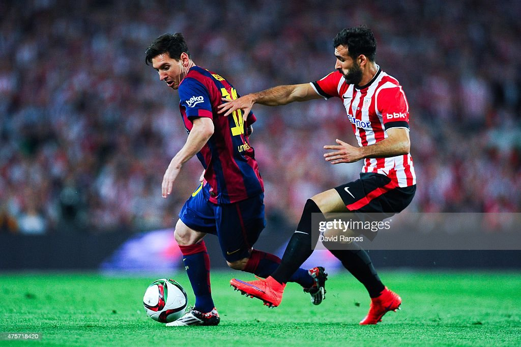 Lionel Messi of FC Barcelona competes for the ball with Mikel Balenziaga of Athletic Club during the Copa del Rey Final match between FC Barcelona...