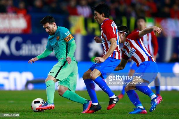 Lionel Messi of FC Barcelona competes for the ball with Nicolas Gaitan of Atletico de Madrid and his teammate Filipe Luis during the Copa del Rey...