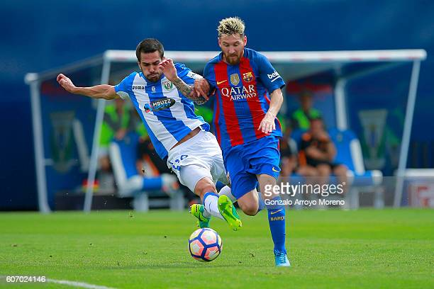 Lionel Messi of FC Barcelona competes for the ball with Pablo Insua of Deportivo Leganes during the La Liga match between Deportivo Leganes and FC...
