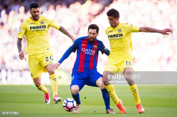 Lionel Messi of FC Barcelona competes for the ball with Roberto Soriano and Rodrigo Hernandez of Villarreal CF during the La Liga match between FC...