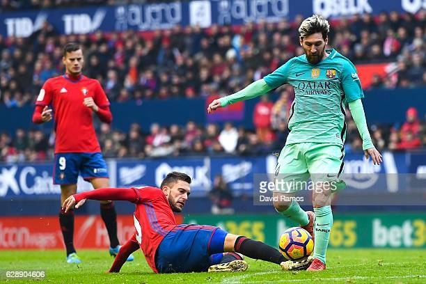 Lionel Messi of FC Barcelona competes for the ball with Roberto Torres of CA Osasuna during the La Liga match between CA Osasuna and FC Barcelona at...