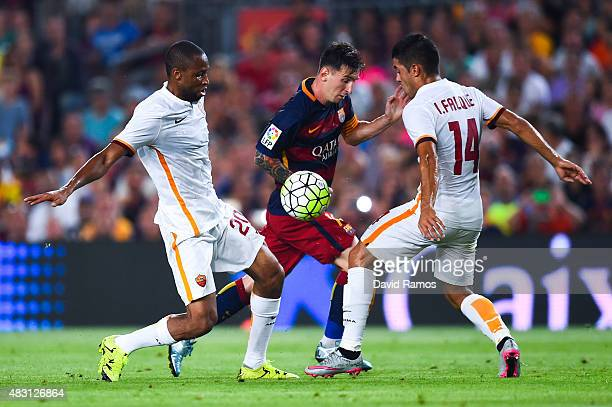 Lionel Messi of FC Barcelona competes for the ball with Seydou Keita and Iago Falque of AS Roma during the Joan Gamper trophy match at Camp Nou on...