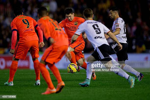 Lionel Messi of FC Barcelona competes for the ball with Shkodran Mustafi of Valencia CF and his teammate Javier Fuego during the La Liga match...