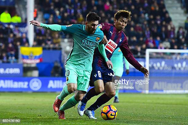 Lionel Messi of FC Barcelona competes for the ball with Takashi Inui of SD Eibar during the La Liga match between SD Eibar and FC Barcelona at Ipurua...