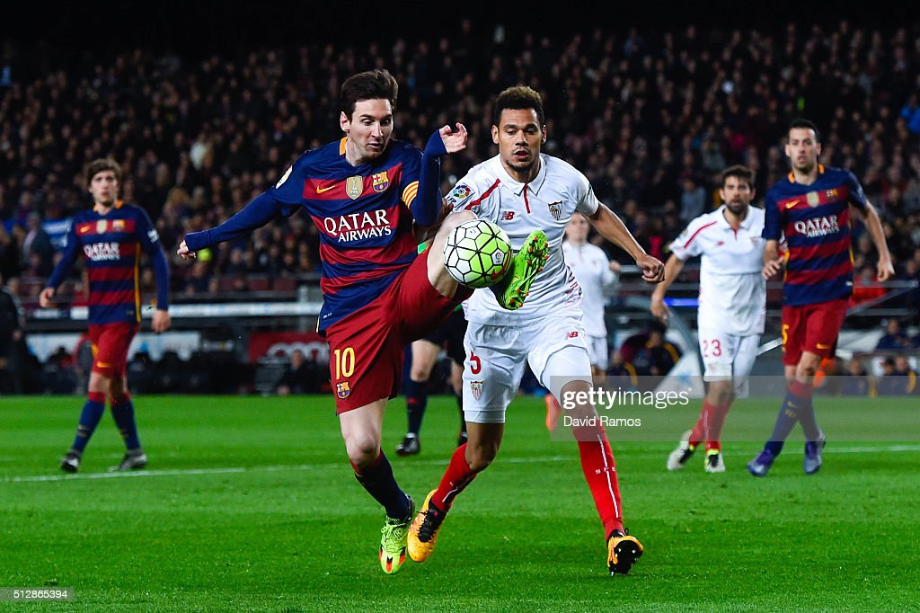 Lionel Messi of FC Barcelona competes for the ball with Timothee Kolo of Sevilla FC during the La Liga match between FC Barcelona and Sevilla FC at...