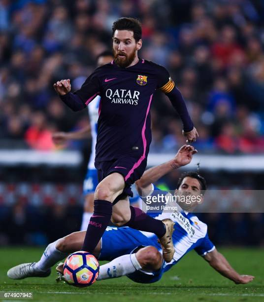 Lionel Messi of FC Barcelona competes for the ball with Victor Sanchez of RCD Espanyol during the La Liga match between RCD Espanyol and FC Barcelona...