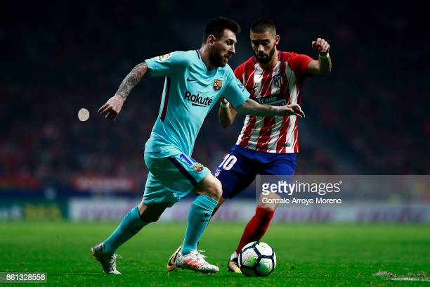 Lionel Messi of FC Barcelona competes for the ball with Yannick Carrasco of Atletico de Madrid during the La Liga match between Club Atletico Madrid...