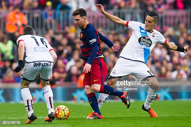Lionel Messi of FC Barcelona conducts the ball between Luis Carlos 'Luisinho' Correia and Faycal Fajr of RC Deportivo La Coruna during the La Liga...