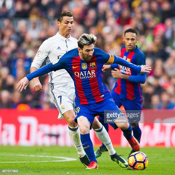 Lionel Messi of FC Barcelona conducts the ball next to Cristiano Ronaldo of Real Madrid CF during the La Liga match between FC Barcelona and Real...