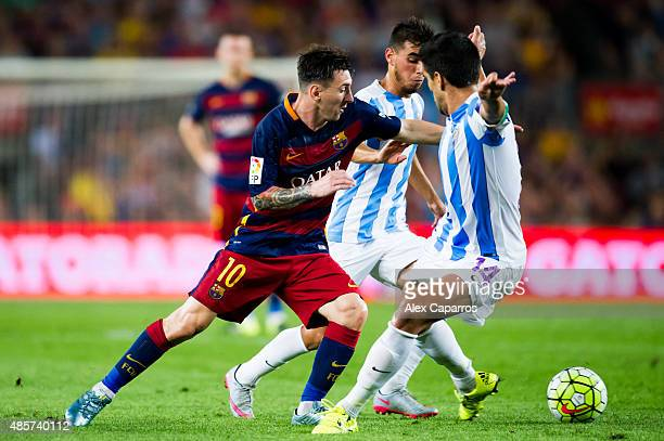 Lionel Messi of FC Barcelona conducts the ball next to Jose Luis Garcia 'Recio' of Malaga CF during the La Liga match between FC Barcelona and Malaga...