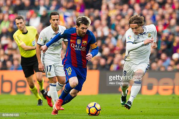 Lionel Messi of FC Barcelona conducts the ball next to Luka Modric of Real Madrid CF during the La Liga match between FC Barcelona and Real Madrid CF...
