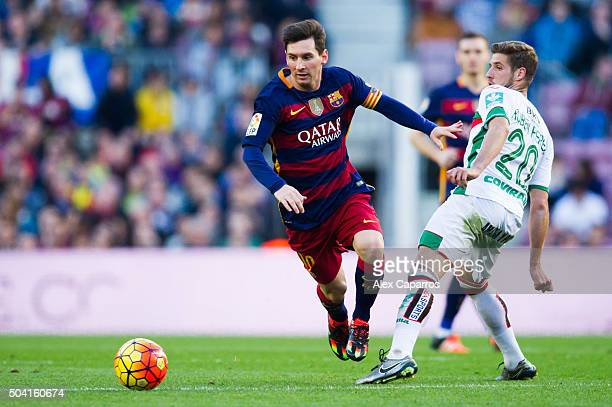 Lionel Messi of FC Barcelona conducts the ball past Ruben Perez of Granada CF during the La Liga match between FC Barcelona and Granada CF at Camp...