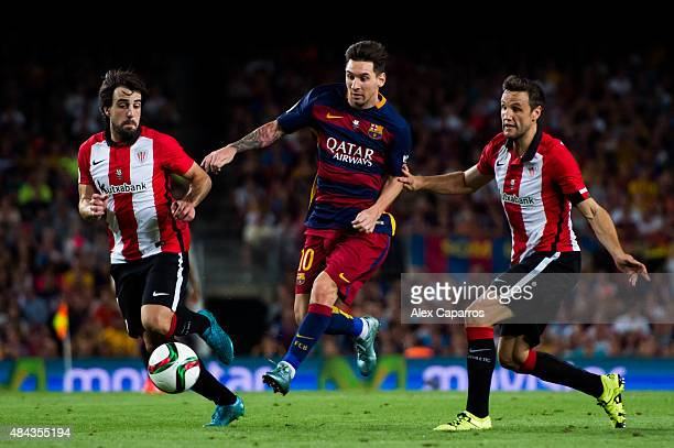 Lionel Messi of FC Barcelona controls the ball between Benat Etxebarria and Carlos Gurpegi of Athletic Club during the Spanish Super Cup second leg...