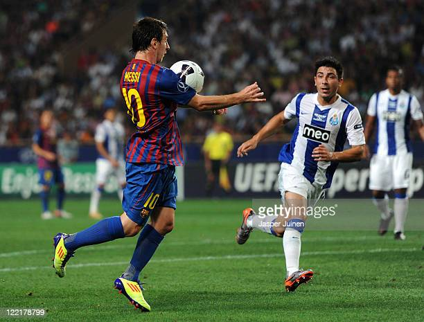 Lionel Messi of FC Barcelona controls the ball next to Jorge Fucile of FC Porto during the UEFA Super Cup match between FC Barcelona and FC Porto at...
