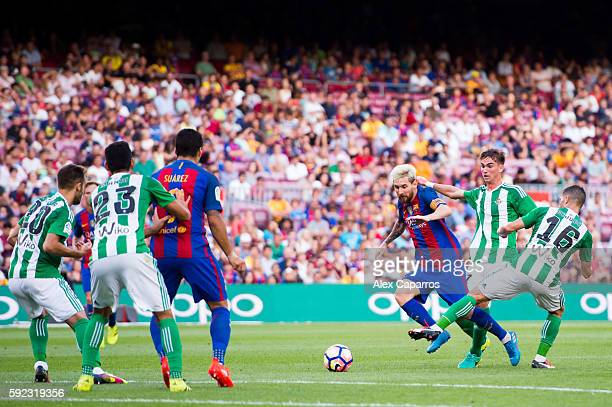 Lionel Messi of FC Barcelona dribbles Fabian Ruiz and Alvaro Cejudo of Real Betis Balompie during the La Liga match between FC Barcelona and Real...