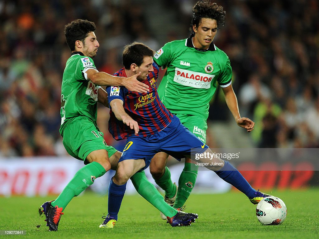 <a gi-track='captionPersonalityLinkClicked' href=/galleries/search?phrase=Lionel+Messi&family=editorial&specificpeople=453305 ng-click='$event.stopPropagation()'>Lionel Messi</a> (C) of FC Barcelona duels for the ball with <a gi-track='captionPersonalityLinkClicked' href=/galleries/search?phrase=Alvaro+Gonzalez+-+Soccer+Player&family=editorial&specificpeople=2261829 ng-click='$event.stopPropagation()'>Alvaro Gonzalez</a> (L) and Edu Bedia of Racing Santander reacts during the la Liga match between FC Barcelona and Real Racing Club at the Camp Nou stadium on October 15, 2011 in Barcelona, Spain.