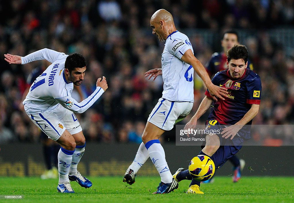 <a gi-track='captionPersonalityLinkClicked' href=/galleries/search?phrase=Lionel+Messi&family=editorial&specificpeople=453305 ng-click='$event.stopPropagation()'>Lionel Messi</a> of FC Barcelona (R) duels for the ball with <a gi-track='captionPersonalityLinkClicked' href=/galleries/search?phrase=Alvaro+Gonzalez+-+Soccer+Player&family=editorial&specificpeople=2261829 ng-click='$event.stopPropagation()'>Alvaro Gonzalez</a> (L) and Jose Maria Movilla of Real Zaragoza during the La Liga match between FC Barcelona and Real Zaragoza at Camp Nou on November 17, 2012 in Barcelona, Spain.