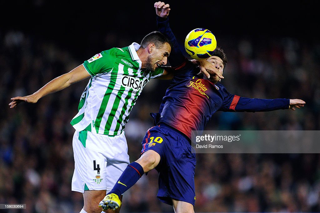 Lionel Messi of FC Barcelona (R) duels for the ball with Antonio Amaya of Real Betis Balompie during the La Liga match between Real Betis Balompie and FC Barcelona at Estadio Benito Villamarin on December 9, 2012 in Seville, Spain.