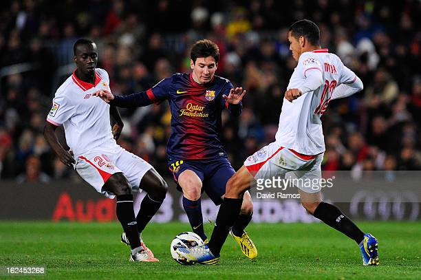 Lionel Messi of FC Barcelona duels for the ball with Baba Diawara and Hedwiges Maduro of Sevilla FC during the La Liga match between FC Barcelona and...