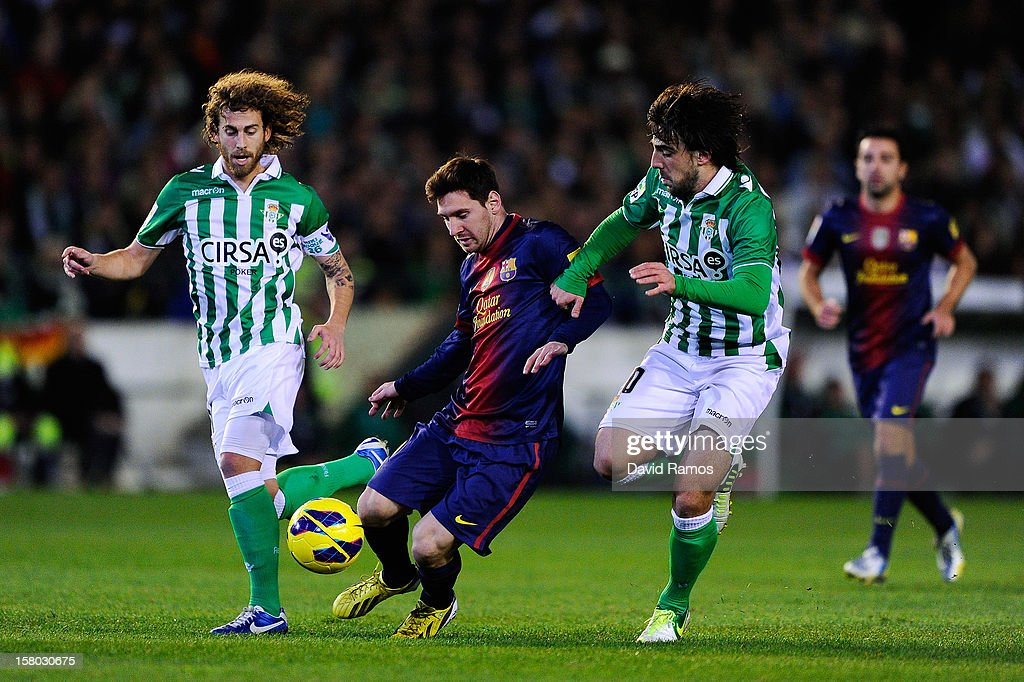Lionel Messi of FC Barcelona (C) duels for the ball with Benat Etxeberria (R) and Jose Alberto Canas of Real Betis Balompieduring the La Liga match between Real Betis Balompie and FC Barcelona at Estadio Benito Villamarin on December 9, 2012 in Seville, Spain.