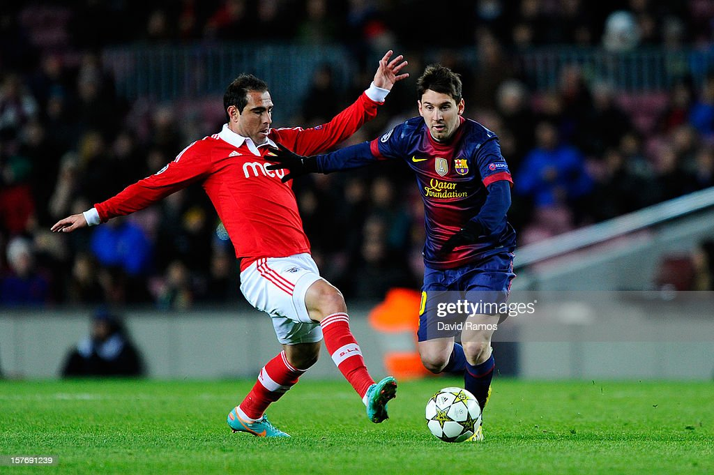 Lionel Messi of FC Barcelona duels for the ball with Bruno Cesar of SL Benfica during the UEFA Champions League Group G match between FC Barcelona and SL Benfica at Nou Camp on December 5, 2012 in Barcelona, Spain.