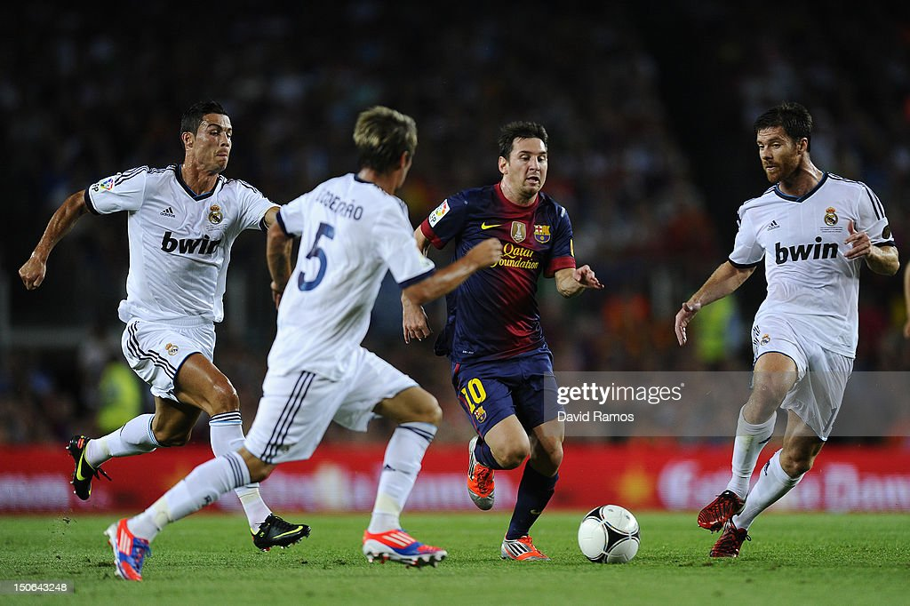 <a gi-track='captionPersonalityLinkClicked' href=/galleries/search?phrase=Lionel+Messi&family=editorial&specificpeople=453305 ng-click='$event.stopPropagation()'>Lionel Messi</a> of FC Barcelona (2ndR) duels for the ball with <a gi-track='captionPersonalityLinkClicked' href=/galleries/search?phrase=Cristiano+Ronaldo+-+Soccer+Player&family=editorial&specificpeople=162689 ng-click='$event.stopPropagation()'>Cristiano Ronaldo</a>, Fabio Coentrao (2ndL) and <a gi-track='captionPersonalityLinkClicked' href=/galleries/search?phrase=Xabi+Alonso&family=editorial&specificpeople=213833 ng-click='$event.stopPropagation()'>Xabi Alonso</a> of Real Madrid CF during the Super Cup first leg match between FC Barcelona and Real Madrid at Camp Nou on August 23, 2012 in Barcelona, Spain.