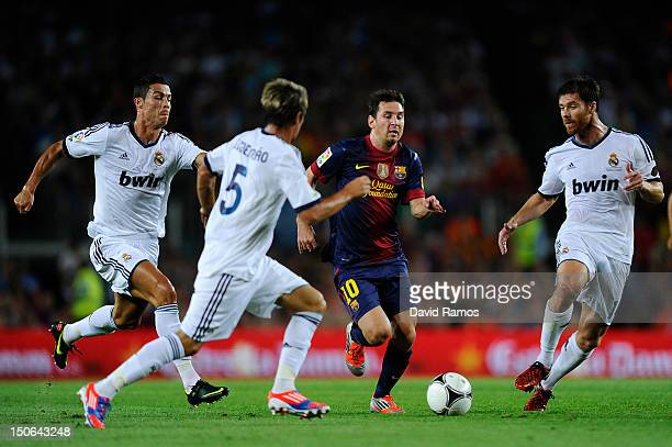 Lionel Messi of FC Barcelona duels for the ball with Cristiano Ronaldo Fabio Coentrao and Xabi Alonso of Real Madrid CF during the Super Cup first...