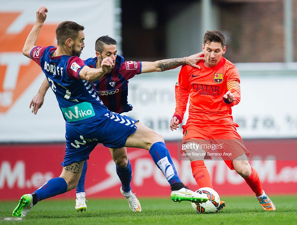 Lionel Messi (R) of FC Barcelona duels for the ball with Didac Vila (C)and Manuel Castellano Lillo'of SD Eibar during the La Liga match between SD Eibar and FC Barcelona at Ipurua Municipal Stadium on March 14, 2015 in Eibar, Spain.