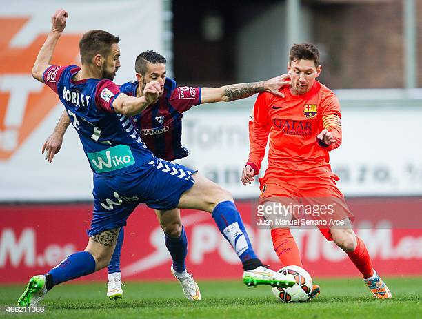 Lionel Messi of FC Barcelona duels for the ball with Didac Vila and Manuel Castellano Lillo'of SD Eibar during the La Liga match between SD Eibar and...