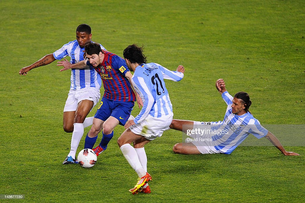 Lionel Messi of FC Barcelona duels for the ball with Eliseu Pereira Sergio Sanchez and Martin Gaston Demichelisof Malaga CF duels for the ball with...