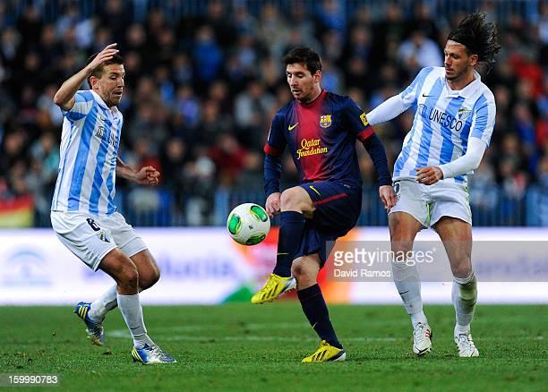 Lionel Messi of FC Barcelona duels for the ball with Ignacio Camacho and Martin Gaston Demichelis of Malaga CF during the Copa del Rey Quarter Final...