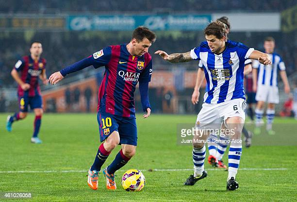Lionel Messi of FC Barcelona duels for the ball with Inigo Martinez of Real Sociedad during the La Liga match between Real Sociedad and Barcelona at...