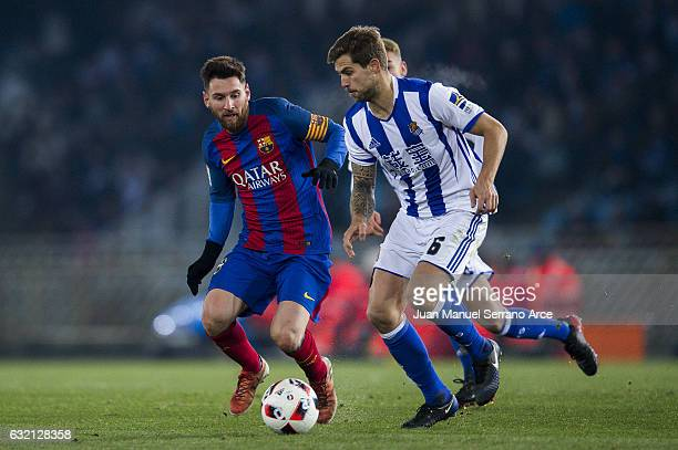 Lionel Messi of FC Barcelona duels for the ball with Inigo Martinez of Real Sociedad during the Copa del Rey Quarter Final First Leg match between...
