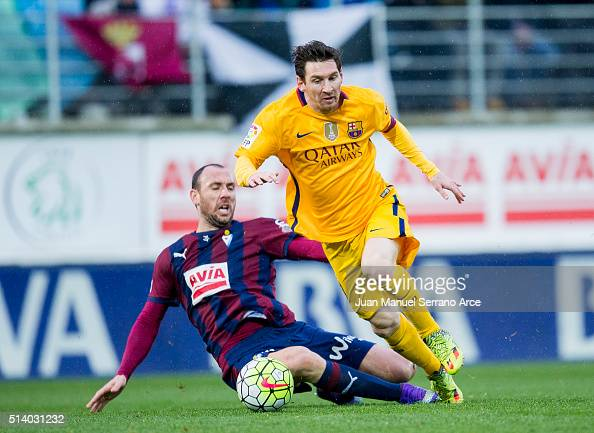 Lionel Messi of FC Barcelona duels for the ball with Ivan Ramis of SD Eibar during the La Liga match between SD Eibar and FC Barcelona at Ipurua...