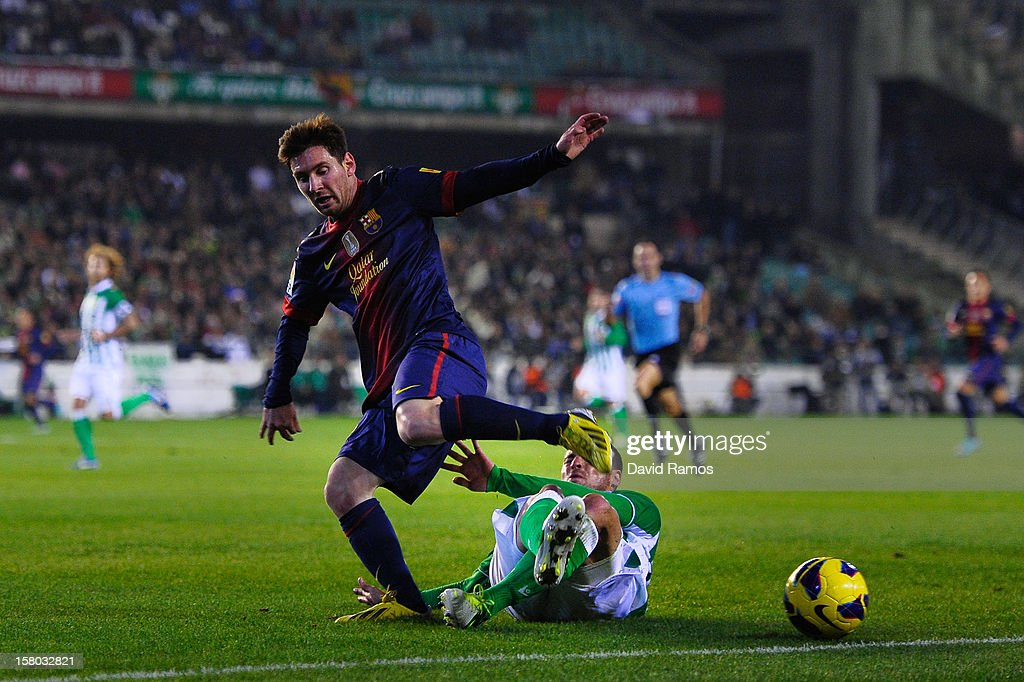 Lionel Messi of FC Barcelona (L) duels for the ball with Javier Chica of Real Betis Balompie during the La Liga match between Real Betis Balompie and FC Barcelona at Estadio Benito Villamarin on December 9, 2012 in Seville, Spain.