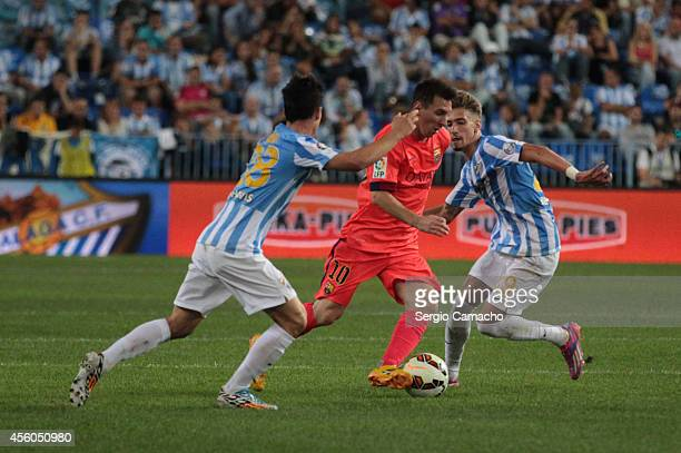 Lionel Messi of FC Barcelona duels for the ball with Juan Pablo Anor alias Juanpi and Samuel Castillejo of Malaga CF during the La Liga match between...