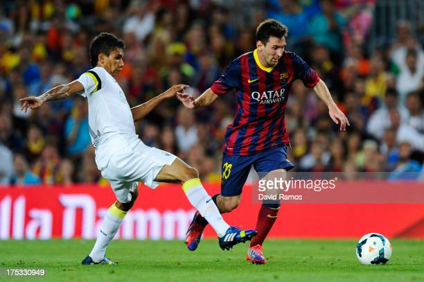 Lionel Messi of FC Barcelona duels for the ball with Leandrinho of Santos during a friendly match between FC Barcelona and Santos at Nou Camp on...