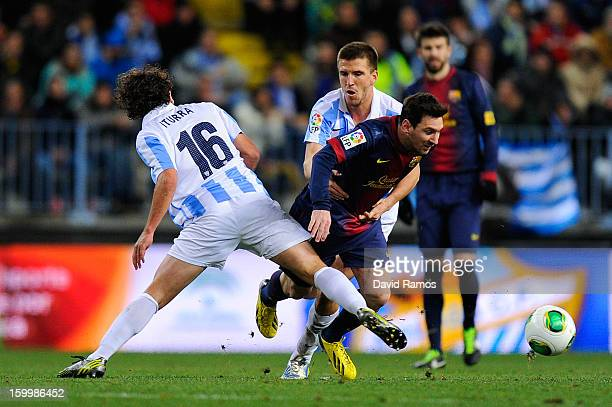 Lionel Messi of FC Barcelona duels for the ball with Manuel Rolando Iturra and Ignacio Camacho of Malaga CF during the Copa del Rey Quarter Final 2nd...