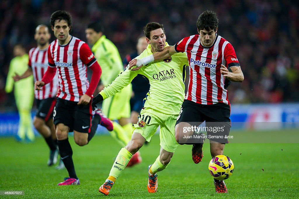 Lionel Messi of FC Barcelona duels for the ball with Mikel San Jose of Athletic Club during the La Liga match between Athletic Club and FC Barcelona...