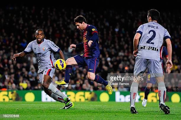 Lionel Messi of FC Barcelona duels for the ball with Raoul Cedric 'Raoul Loe' of CA Osasuna during the La Liga match between FC Barcelona and CA...