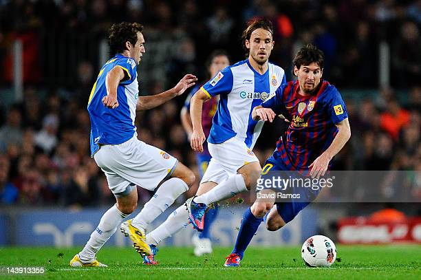 Lionel Messi of FC Barcelona duels for the ball with Raul Baena of RCD Espanyol and Joan Verdu of RCD Espanyol during the La Liga match between FC...