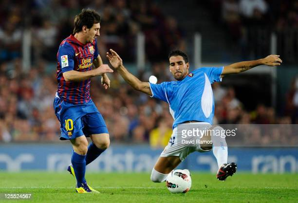 Lionel Messi of FC Barcelona duels for the ball with Raul Garcia Escudero of CA Osasuna during the La Liga soccer match between FC Barcelona and CA...