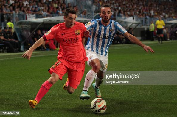 Lionel Messi of FC Barcelona duels for the ball with Sergi Darder of Malaga CF during the La Liga match between Malaga CF and FC Barcelona at La...