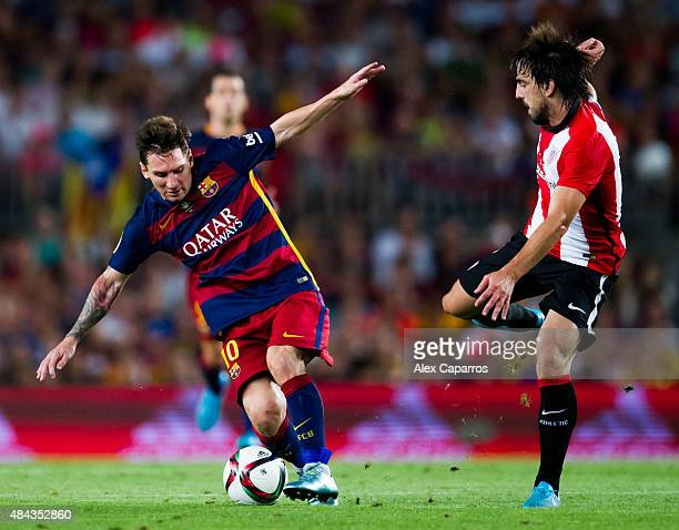 Lionel Messi of FC Barcelona fights for the ball with Benat Etxebarria of Athletic Club during the Spanish Super Cup second leg match between FC...